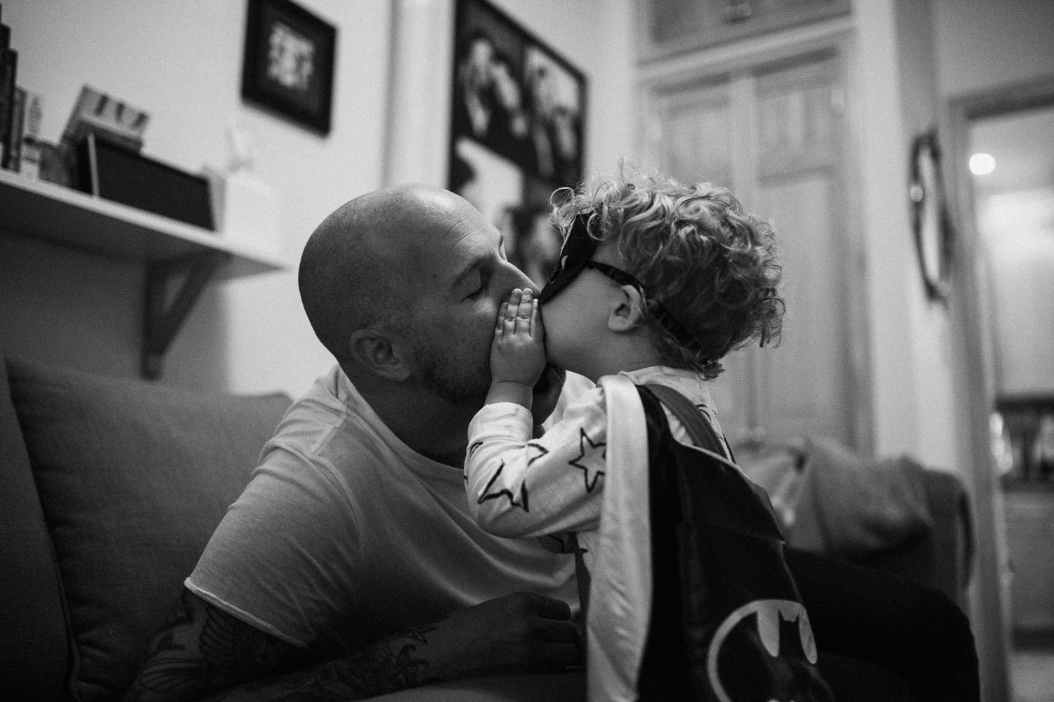candid-black-and-white-photo-little-boy-in-batman-costume-kissing-dad-slc-utah