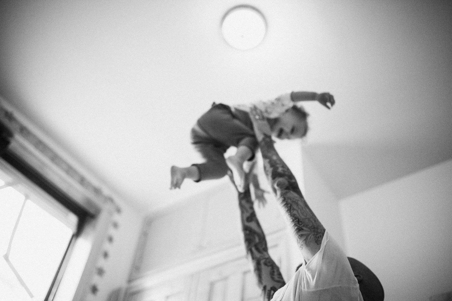 natural-and-artistic-black-and-white-playful-photo-father-tossing-child-in-air-slc-ut