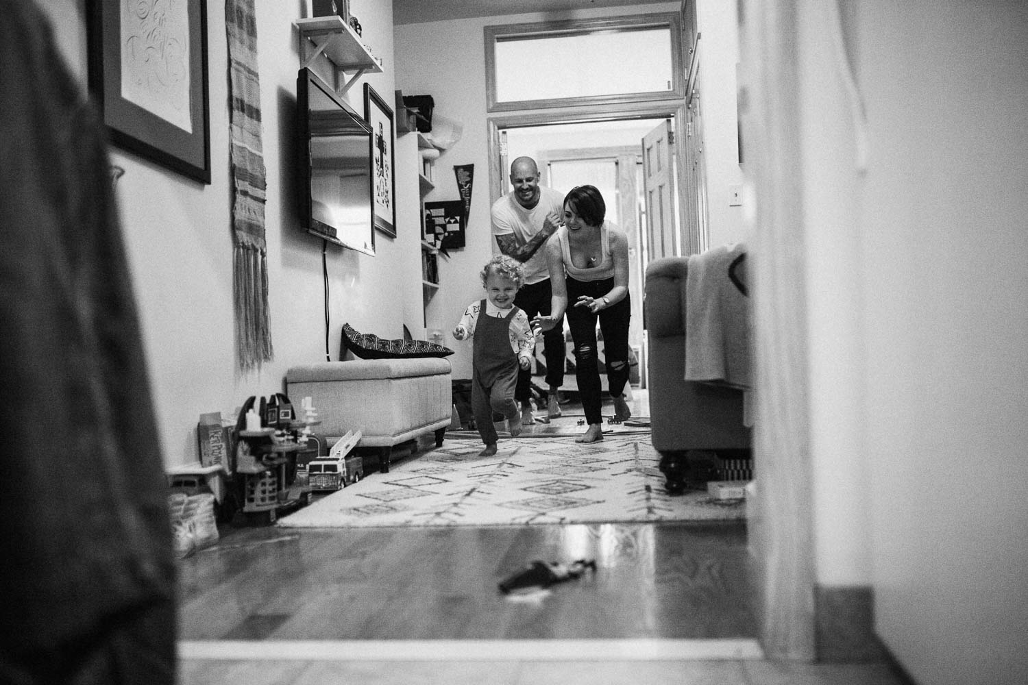 candid-playful-family-moment-chasing-through-the-house-black-and-white-salt-lake-ut