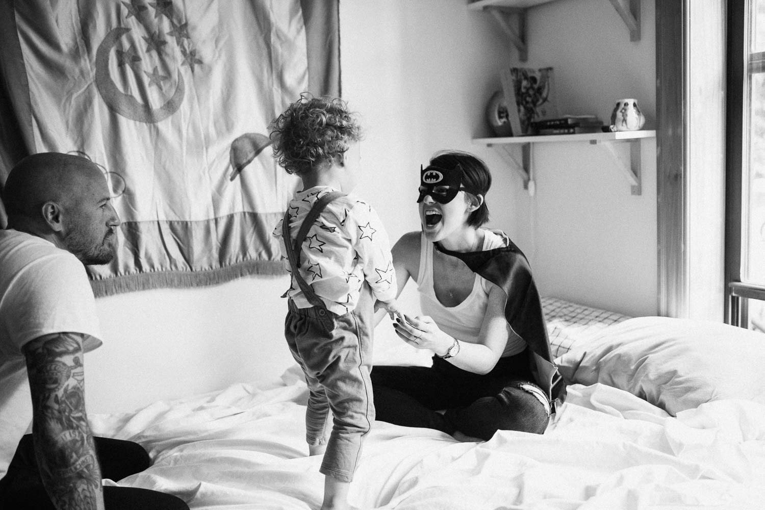candid-black-and-white-playful-moment-between-mother-and-son-on-bed-during-in-home-session-with-jen-fairchild-photography-salt-lake-city-utah