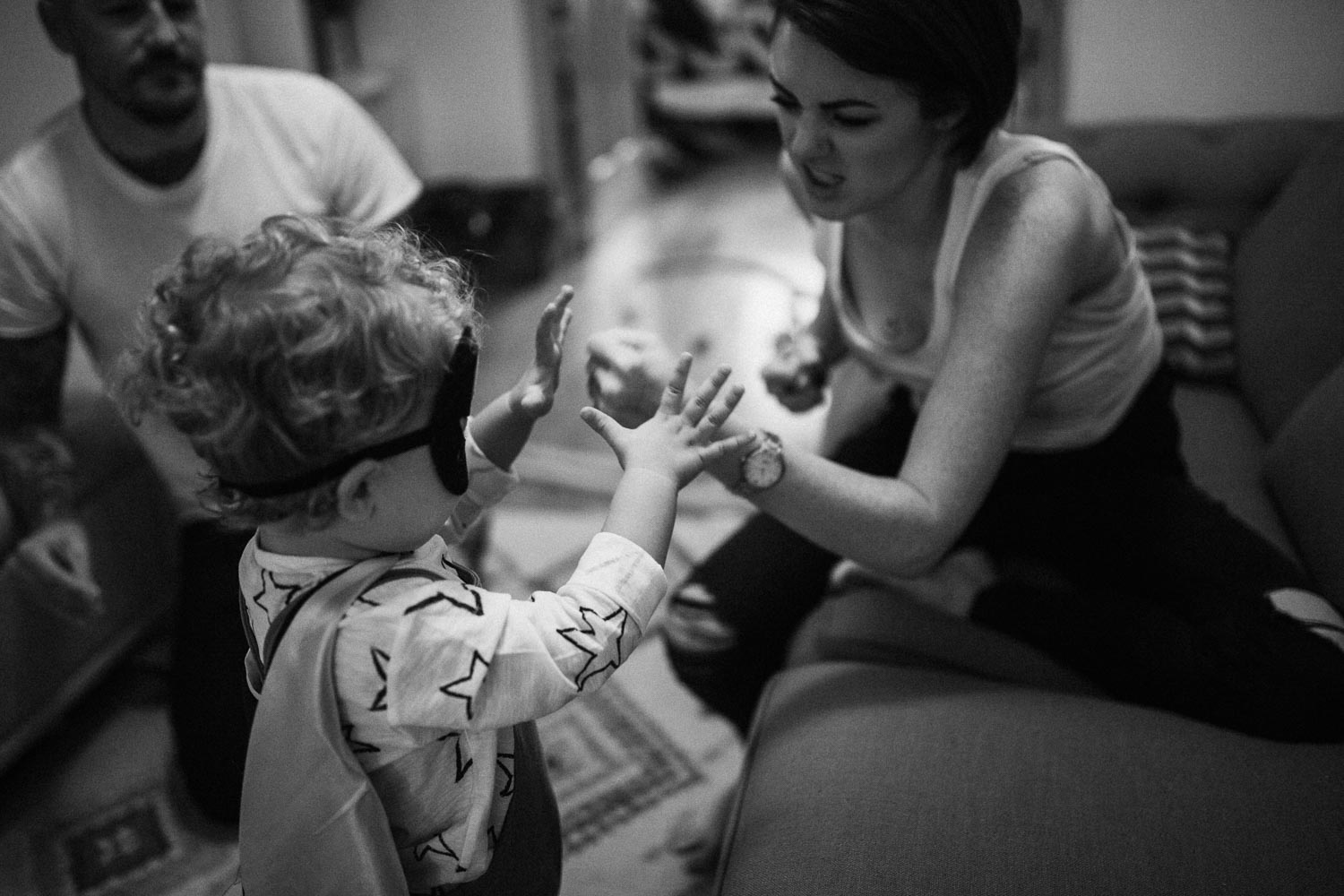 candid-black-and-white-photo-little-boy-in-batman-costume-pretend-fighting-with-mom-slc-utah