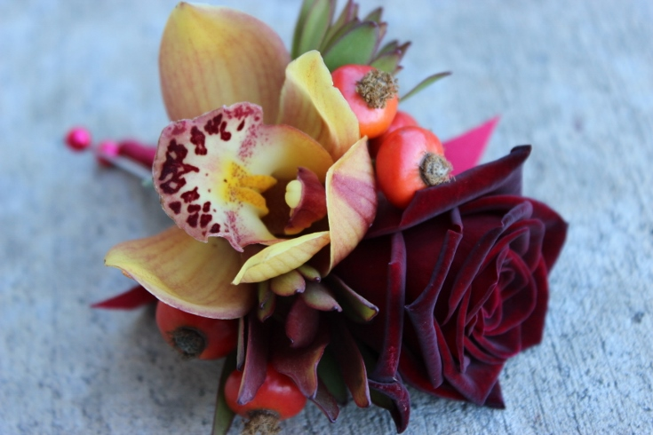 grooms boutonniere black roses rose hips red berries and orchid