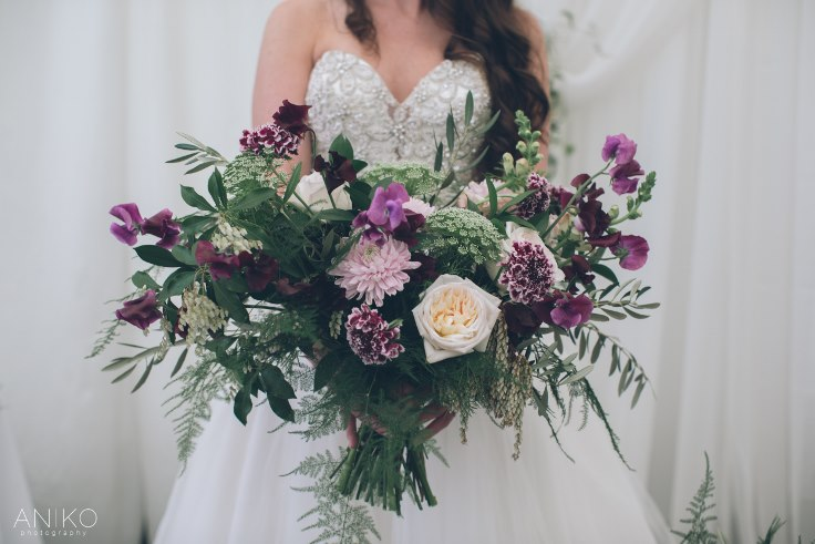 sophisticated floral designs purple spring bridal bouquet with foliage sweet peas pieris scabiosa and olive