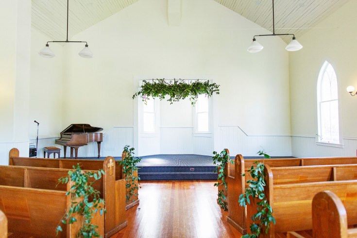 sophisticated floral designs portland oregon wedding florist military wedding bell tower chapel greenery floral hanging installation ceremony decor greenery aisle decor vines garland