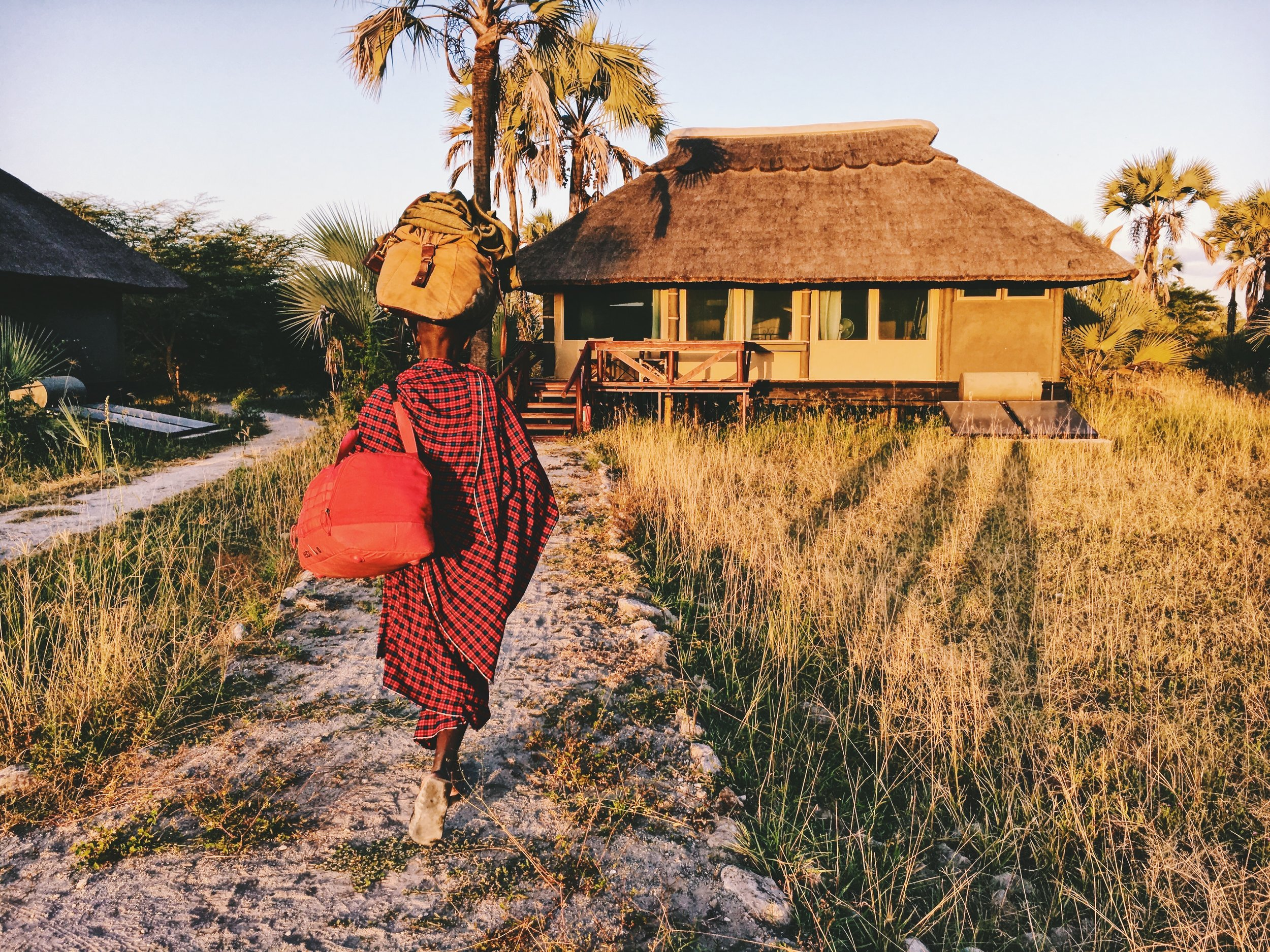 a masai tribe member carrying both of our two weeks worth of luggage! -