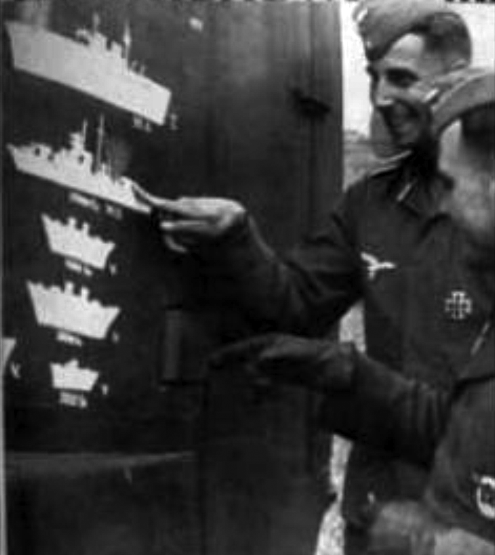 German officers point at the tailplane of a Ju88 carrying the outline of a British aircraft carrier. The picture was likely taken in March 1941, after HMS Illustrious had been hit - but also after several claimed hits against HMS Formidable.