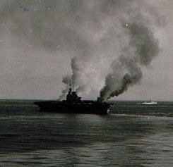 HMS INDOMITABLE comes about to bring the wind over the deck to blow smoke from the fires raging fore and aft away from the ship.
