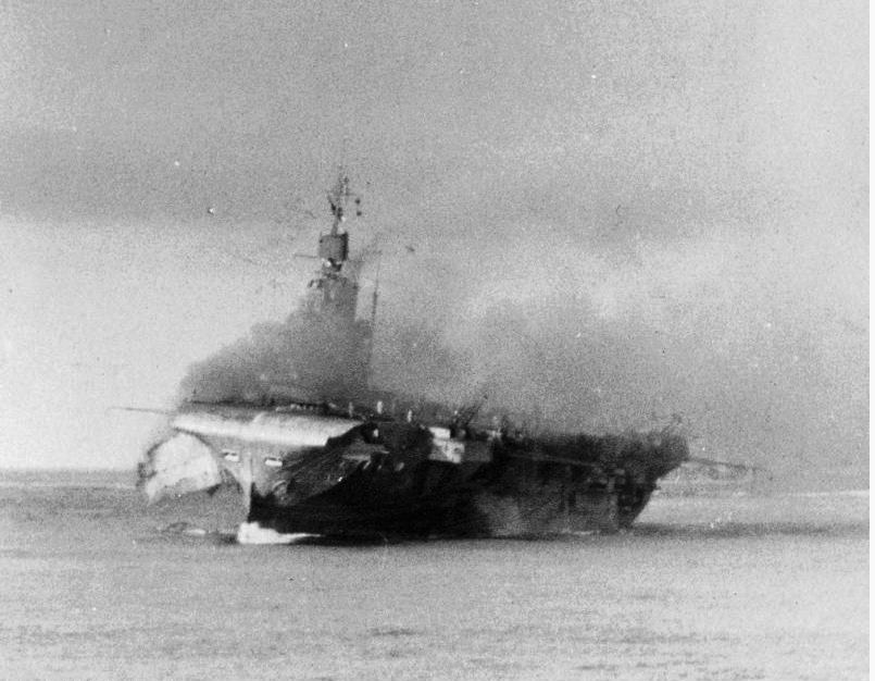 "A large flap of hull plating dangles out from the starboard forward section of Indomitable, blasted outward by the 550lb GP bomb and subsequent detonation of the 4.5in shells in ""A1"" Ready Use locker.."