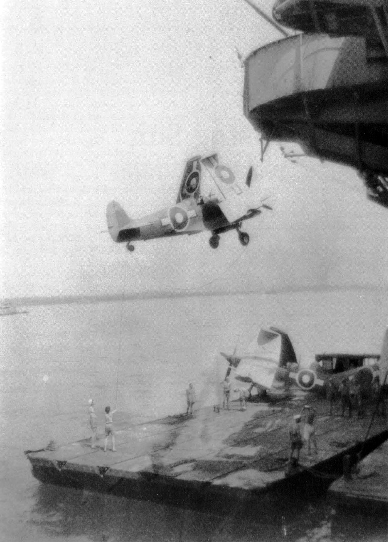 A Seafire is slung over the side of what may be HMS UNICORN before being positioned aboard a lighter for transfer in Leyte Harbour.