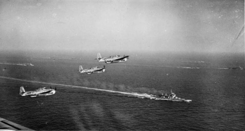 Avengers fly above the British Pacific Fleet. In the foreground is HMS KING GEORGE V or HOWE.