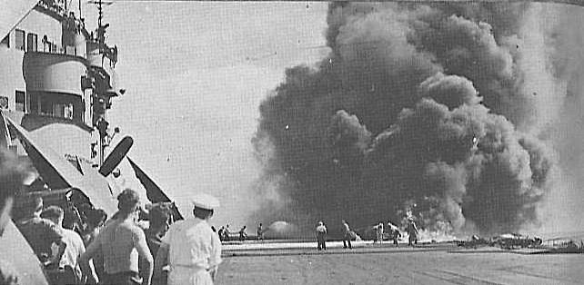 Firefighters tackle the blaze started by a kamikaze collision on HMS VICTORIOUS' aft flight deck. Also note VICTORIOUS' lack of ant-flash gear discipline in comparison to FORMIDABLE's crew.
