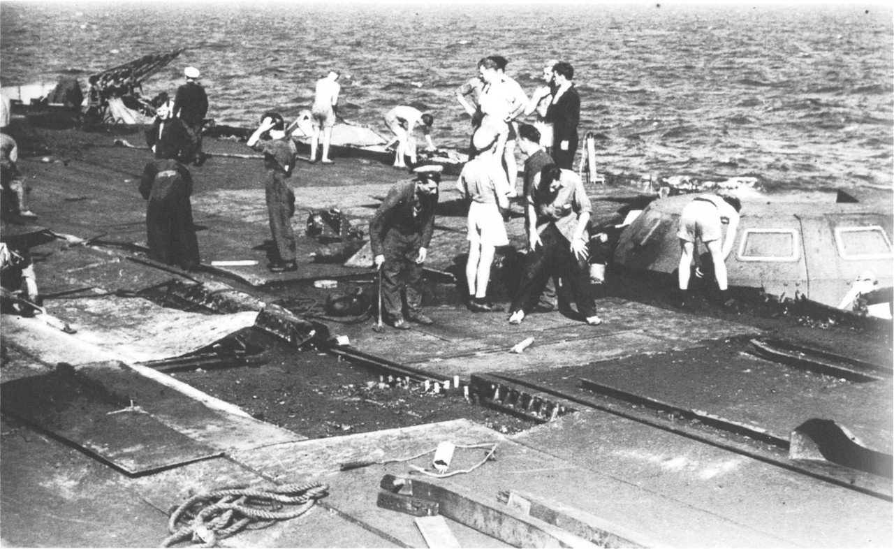 Damage control teams work on replacing the damaged plate steel alongside HMS VICTORIOUS' disabled B2 4.5in turret. The wrecked accelerator is clearly visible in the middle ground.