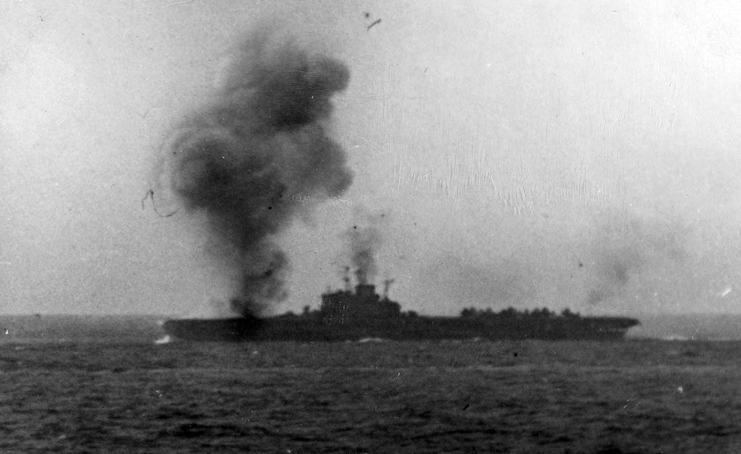 HMS VICTORIOUS burns in the vicinity of B2 4.5in turret on the port bow after being hit by a kamikaze on May 9. The prominent director in front of her island was moved there from on top of the bridge to provide space for new radar equipment. HMS Formidable received a similar modification, but HMS Illustrious and Indomitable did not.