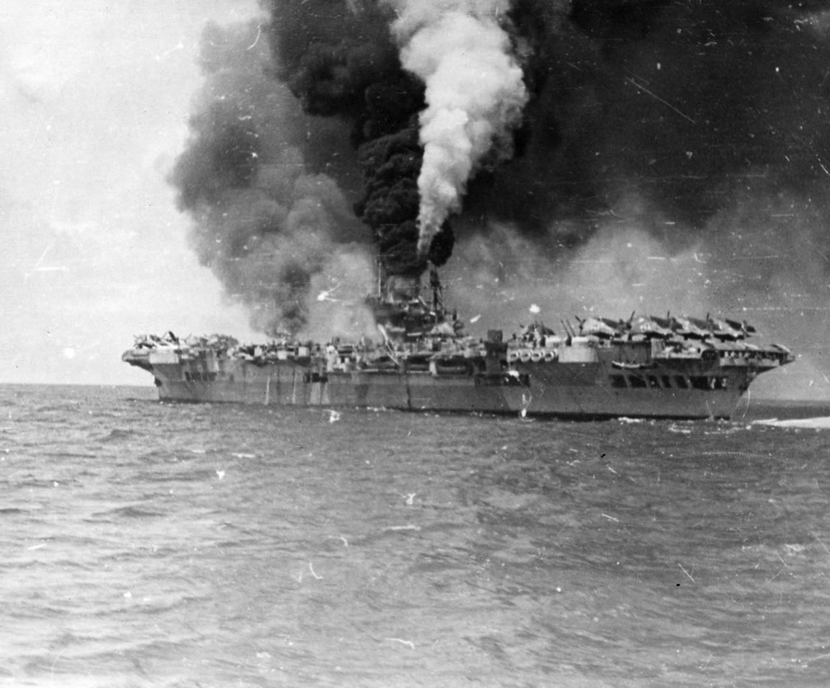 HMS Formidable on fire after the kamikaze strike. The three tones of grey in the smoke rising from the ship tell different stories. The grey is from the burning wreckage of aircraft and fuel on the flight deck. The black oily soot is from Formidable's funnel. The white is steam being vented via emergency systems from the damaged central boiler room.