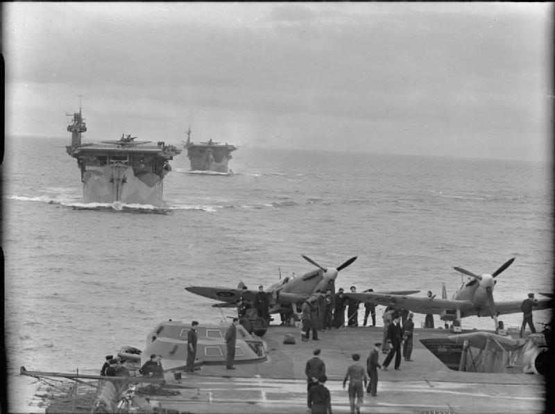 Aircraft carriers HMS BITER and HMS AVENGER underway in line astern from HMS VICTORIOUS. Two Supermarine Seafires of No 884 Squadron, Fleet Air Arm can be seen at the far end of the flight deck of HMS VICTORIOUS.