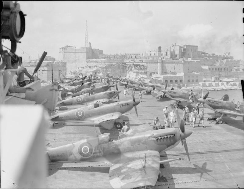 Under the bombed bastions of the entrance to Grand Harbour, Valletta, Malta, an escort carrier arrives with the deck loaded with Supermarine Seafire IIIs (recognisable by their detached wingtips).