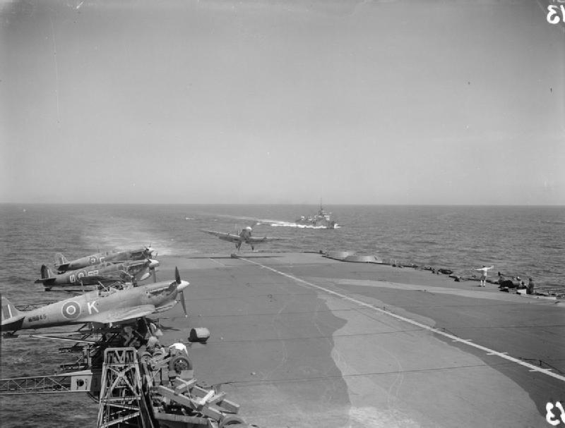 "A Supermarine Seafire of No 885 Squadron Fleet Air Arm just about to ""land out"" on the deck of HMS FORMIDABLE at Gibraltar. Three more Seafires are ranged on outriggers on the side of the Flight Deck."