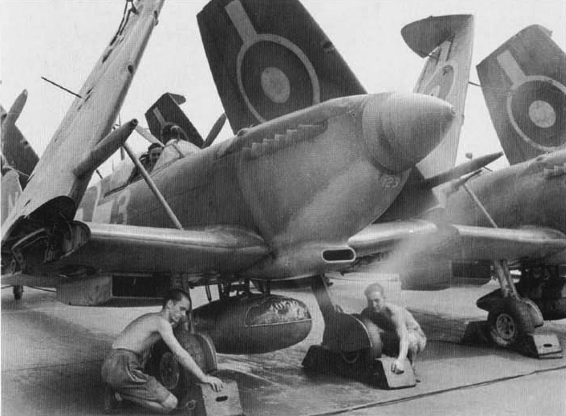 A Royal Navy Fleet Air Arm Seafire fighter being warmed up on board the aircraft carrier HMS Implacable while ratings hold chocks under the wheels. The 89 gallon ex P-40 Warhawk drop tank is prominent.