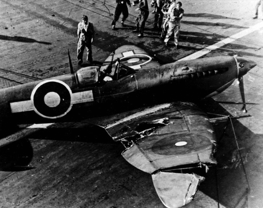 A crashed Seafire aboard HMS INDEFATIGABLE. A large chunk of its wing can be seen to have been carried away by gunfire. The presence of the SEAC roundel on the right wing simply represents the use of a spare wing component not painted for the Pacific theatre.