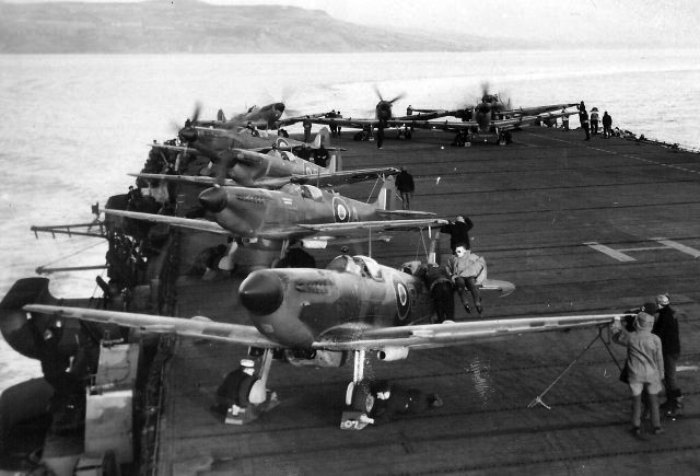 "Seafires aboard HMS HUNTER. Note the ""slipper"" fuel tanks under the fuselage."