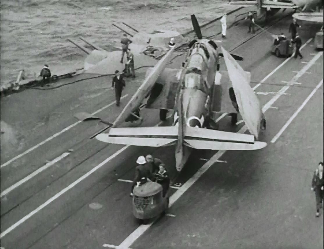 An Avenger is wheeled into the forward deck park, probably aboard HMS FORMIDABLE