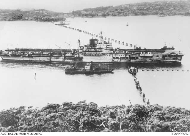 HMS FORMIDABLE passing through the Sydney Harbour anti-submarine boom net in 1945. The blackened funnel is due to scorch damage from a kamikaze attack.