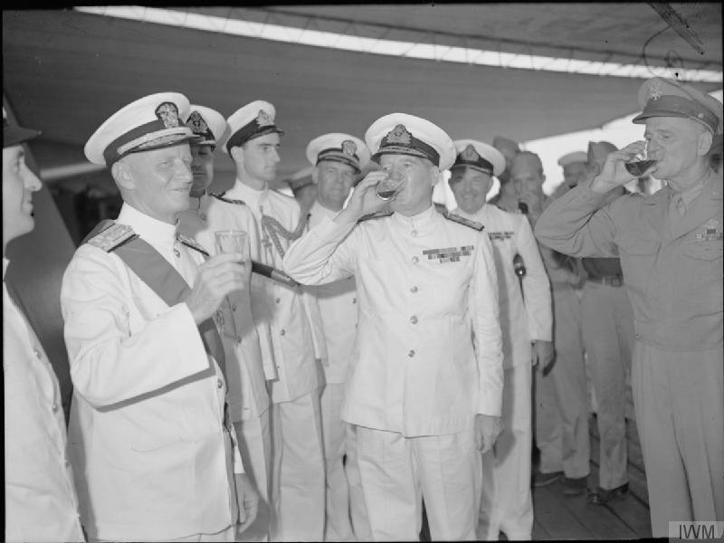 Admiral Nimitz (left), Admiral Sir Bruce Fraser and General Spaatz take a tot of rum with the ship's company of HMS DUKE OF YORK.
