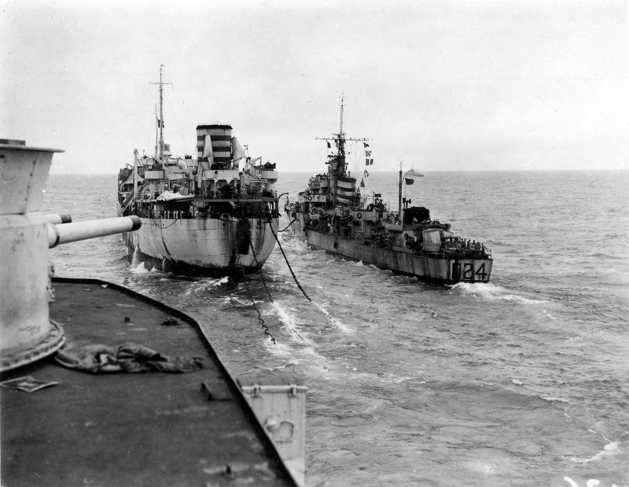 The destroyer HMS ULYSSES refuels alongside a Royal Navy auxiliary as a carrier, either HMS INDEFATIGABLE or IMPLACABLE approaches.