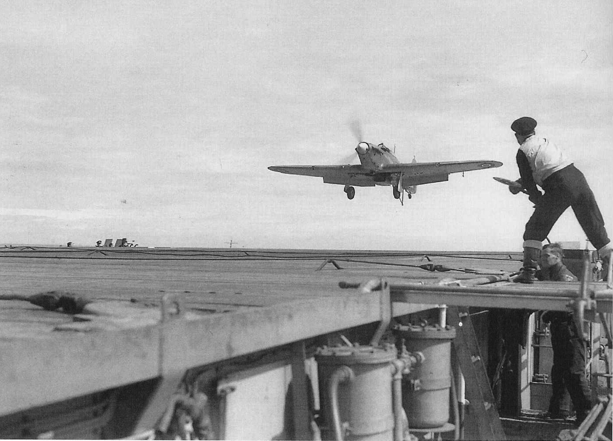 A signalman gives the 'cut engine' signal to an approaching Sea Hurricane.