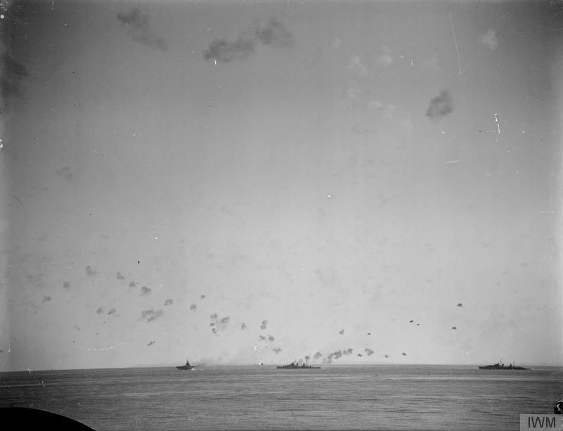 Two anti-aircraft cruisers join one of the armoured carriers, probably VICTORIOUS, in laying down a defensive barrage.