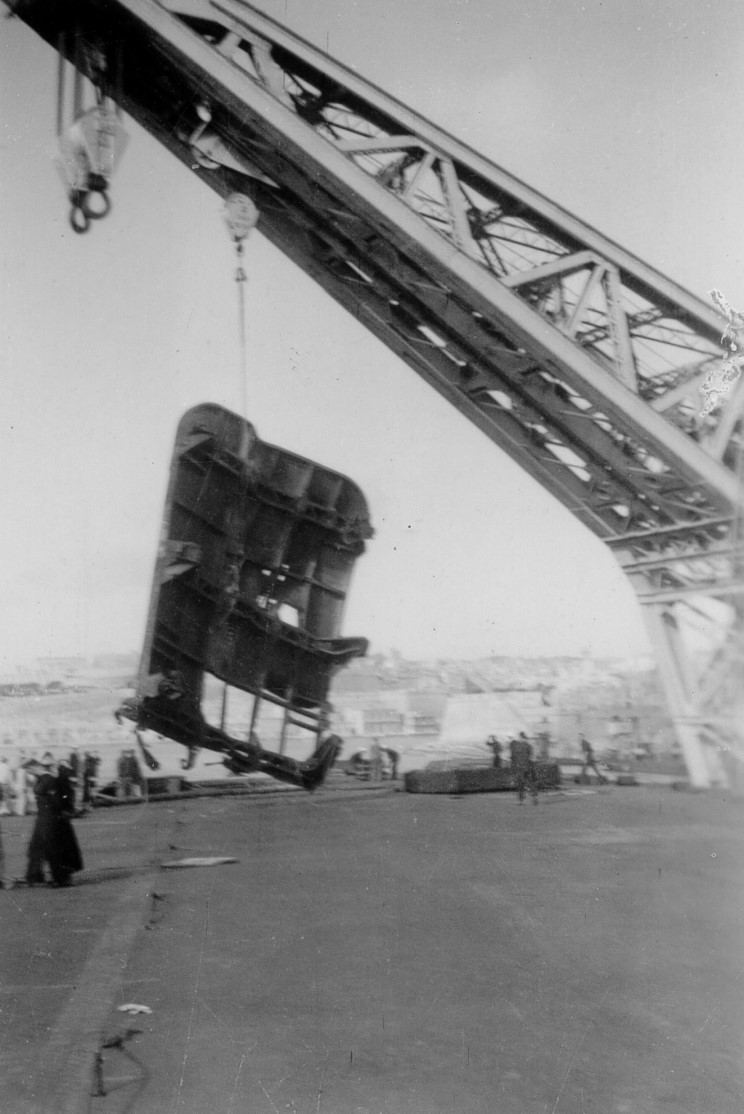 Malta's crane hoists the toppled lift platformout of ILLUSTRIOUS's shattered aft lift well. The lighter-coloured square patch in the bottom left of the picture appears to be covering the 2200lbs bomb penetration hole. The sailor to its left seems to be resting his foot on a small raised section - roughly where the apparently 'petaled' metal was in the famous photo showing ILLUSTRIOUS's burning deck.