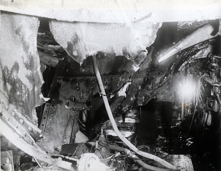 A view through the hole in the 1in Hangar Deck showing the holes in the Upper Deck (Wardroom Flat) below to the Link Trainer Compartment.