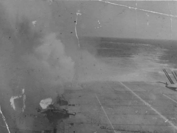 """This picture, while sometimes captioned as being HMS ILLUSTRIOUS, is also sometimes captioned HMS FORMIDABLE. The scene matches very closely with that of a caption listed for a missing photo from FORMIDABLE's National Archives AdmiraltyDamage Report: """" B.1. Hit starboard side aft. Bomb bursting under water."""""""