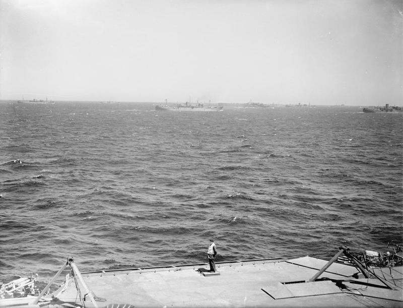 A deck officer observes flight activities with the Pedestal convoy in the background.