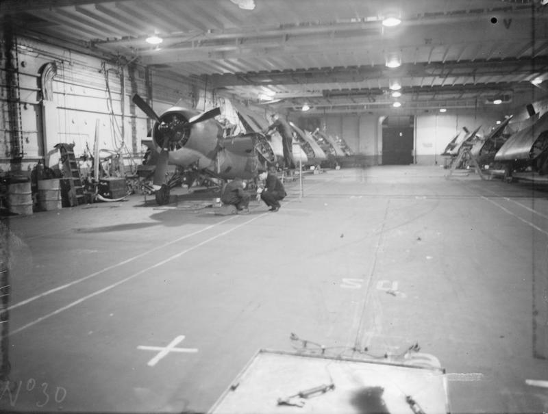 Martlets folded in the hangar of HMS VICTORIOUS in September, 1942. Note the partially closed armoured roller doors to the lift in the background.