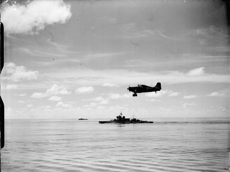 A Grumman Martlet fighter of 888 Squadron, Fleet Air Arm from the aircraft carrier FORMIDABLE flying over HMS WARSPITE while circling to land during operations round Madagascar.
