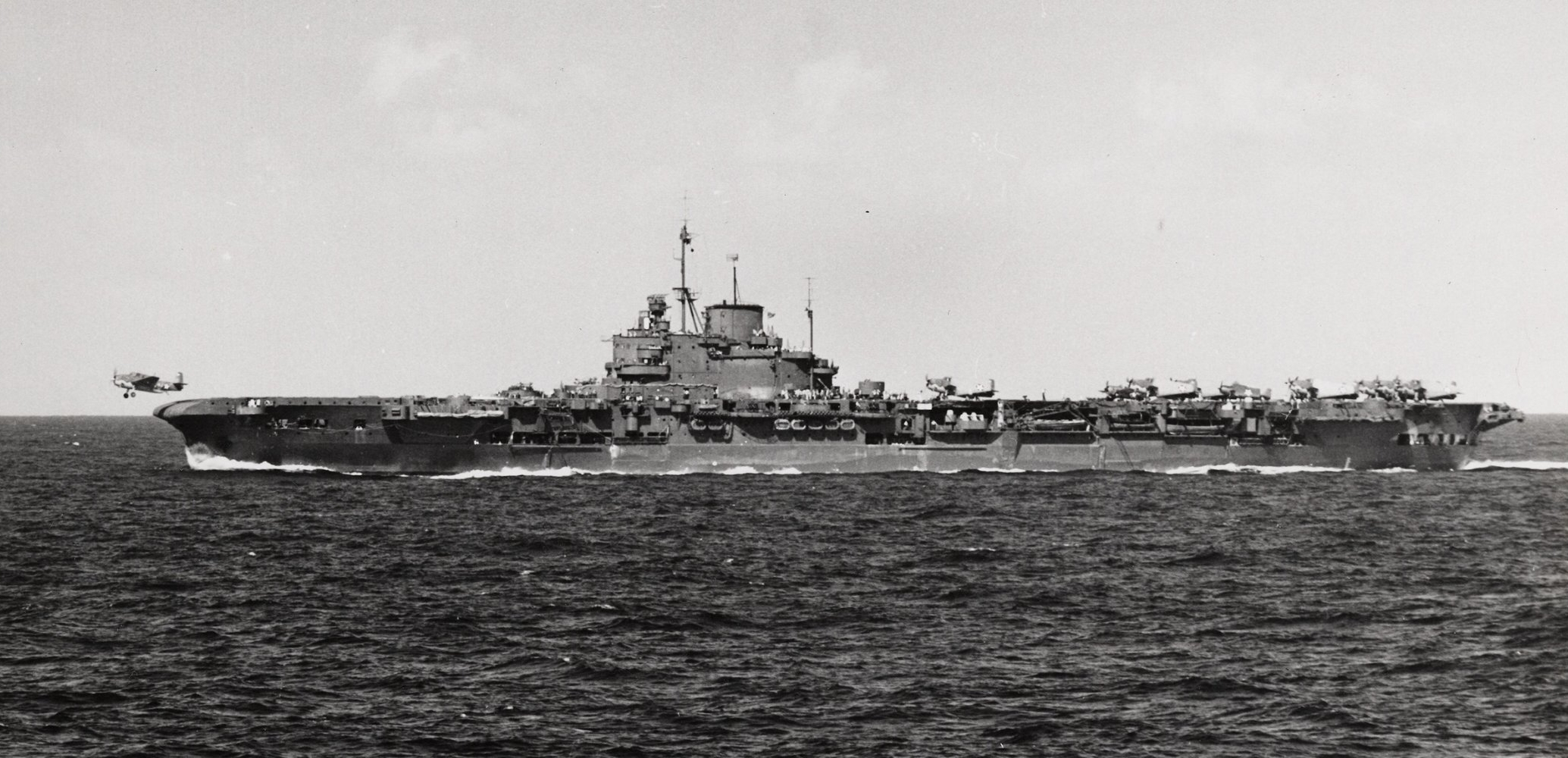 'USS ROBIN' (HMS VICTORIOUS) flies off a Martlet. Avengers can be seen in the rear deck park.