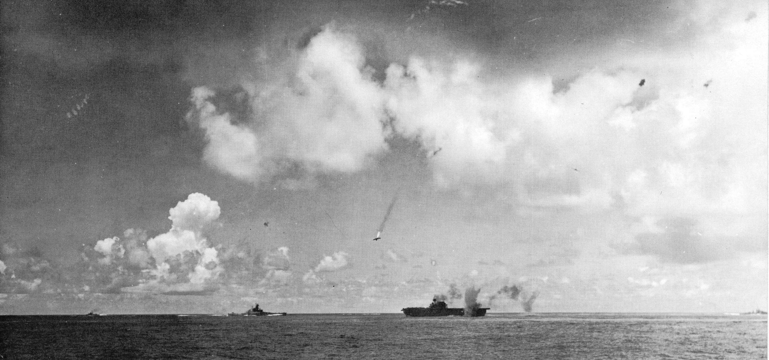 A Japanese bomber is shot down in flames as USS ENTERPRISE suffers a near-miss during the battle of Santa Cruz.