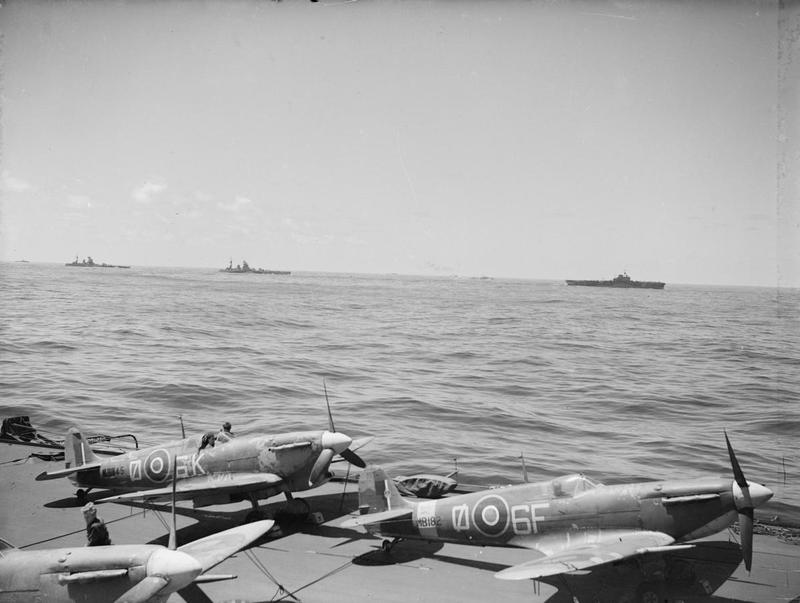 HMS INDOMITABLE is seen over the Seafire 'ready' park aboard HMS FORMIDABLE, with the battleships RODNEY and NELSON. Force 'H' is pictured here in the Ionian Sea just hours before INDOMITABLE was torpedoed.