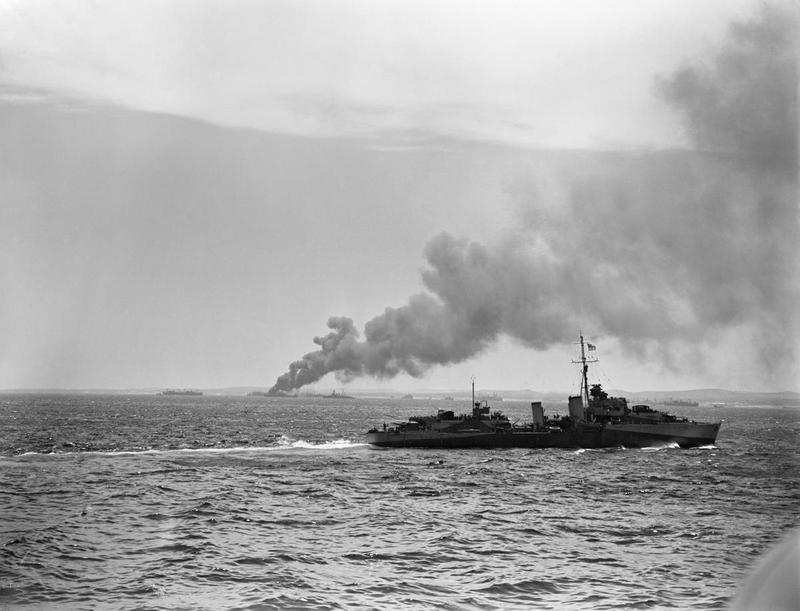 The Sicily Landings 9-10 July 1943: HMS ESKIMO patrolling the landing area off the coast of Sicily, while in the distance a supply ship burns after being hit by enemy aircraft.