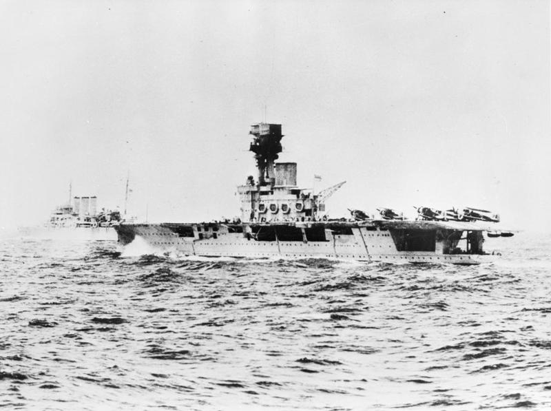 HMS HERMES, with Swordfish ranged on deck, is pictured while at sea to the south of Ceylon in the company of a heavy cruiser, shortly before she was lost in April 1942.