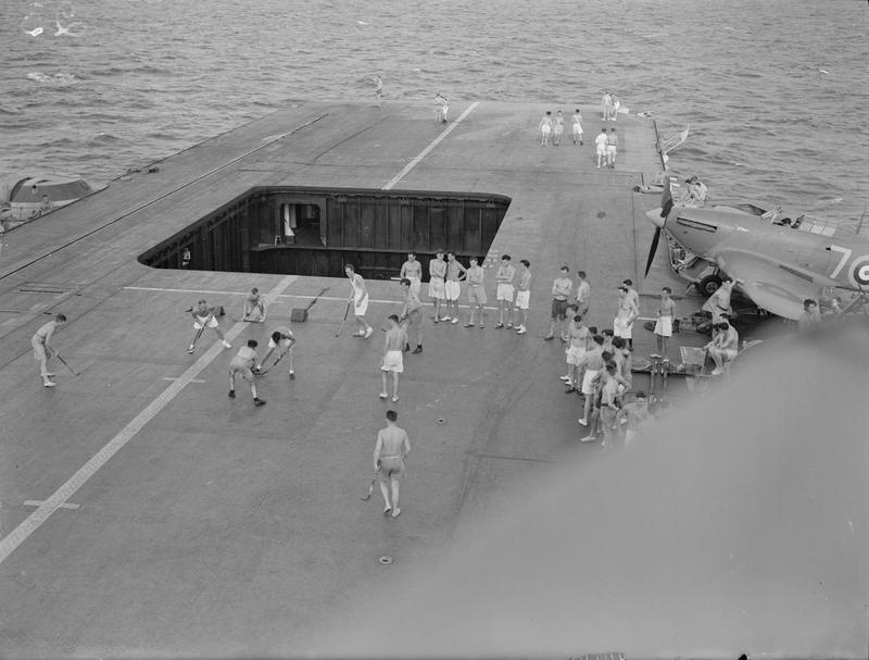 A game of deck hockey on the flight deck of HMS INDOMITABLE. Note the Sea Hurricane on its outrigger between S1 Pom Pom and the 4.5in turrets. The airlock part-way down the lift-well is for rapid access to the forward medical station.