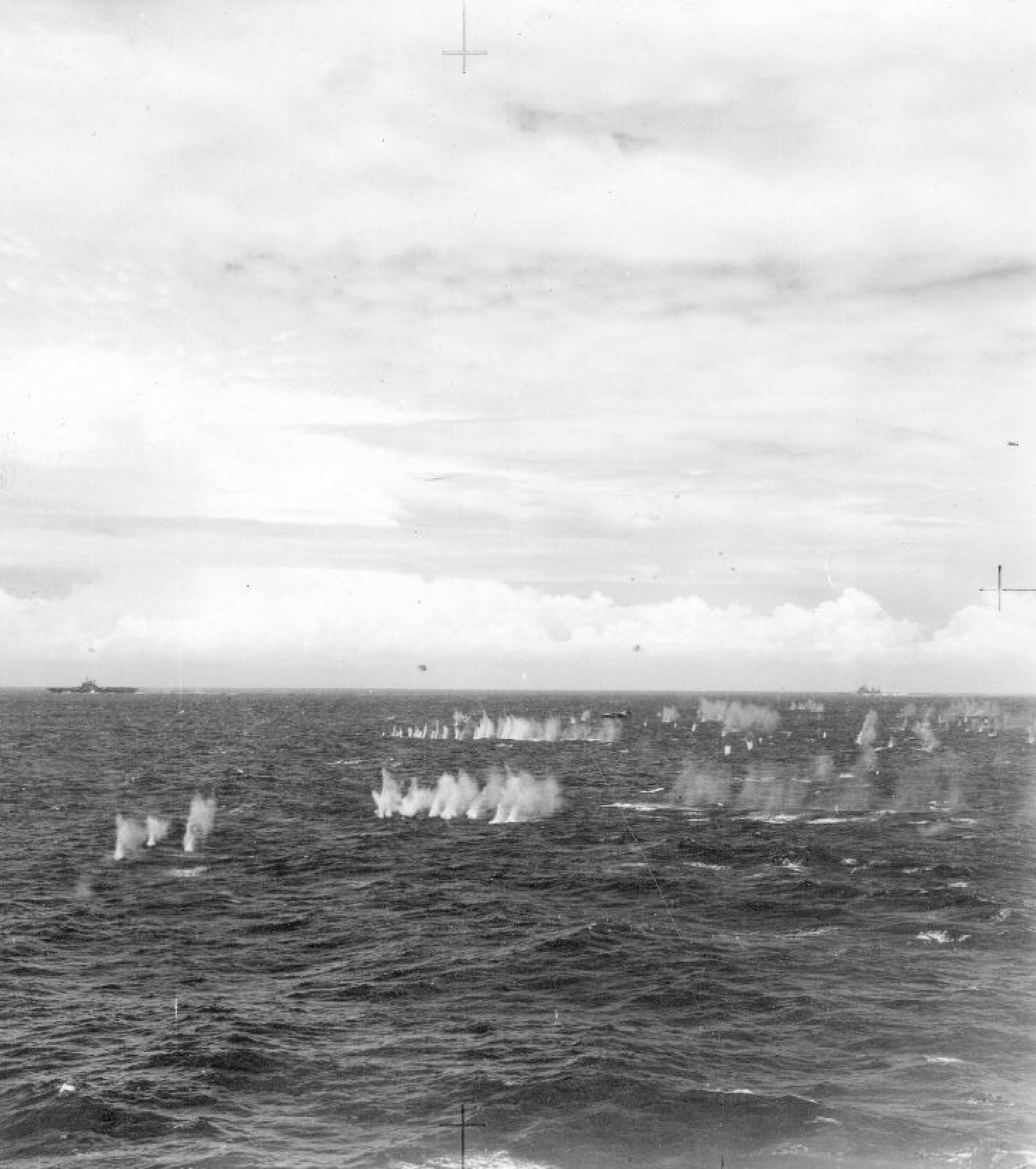 A Ki-21 'Sally' bomber is surrounded by spray kicked up by the close-range anti-aircraft armaments of British Pacific Fleet carriers and escorts. A Seafire can be seen climbing out of the close-defence zone on the right-edge of the picture. This Sally, and up to six others, were shot down. This picture is taken from HMS INDEFATIGABLE, with an unidentified armoured carrier and the battleship King George V in the background.