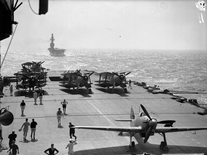 HMS EAGLE seen from the flight deck of HMS INDOMITABLE. Fairey Albacores and Hawker Hurricanes can be seen on the deck of INDOMITABLE, during a Malta convoy.