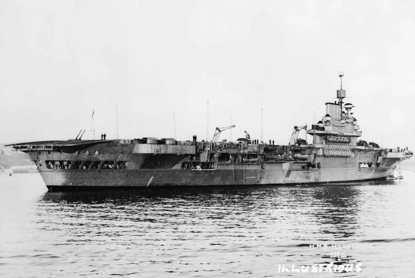 A newly completed HMS ILLUSTRIOUS in Plymouth Sound, June 1940. Note the port-side aft 4.5in turret, with guns elevated and aimed over the aft flight deck.