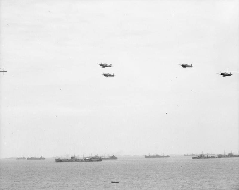 FAA Hellcats flying over the Fleet Train, the supply ships which service the warships of the Pacific Fleet. The ships shown include oilers, storeships, ammunition ships and their escorts.