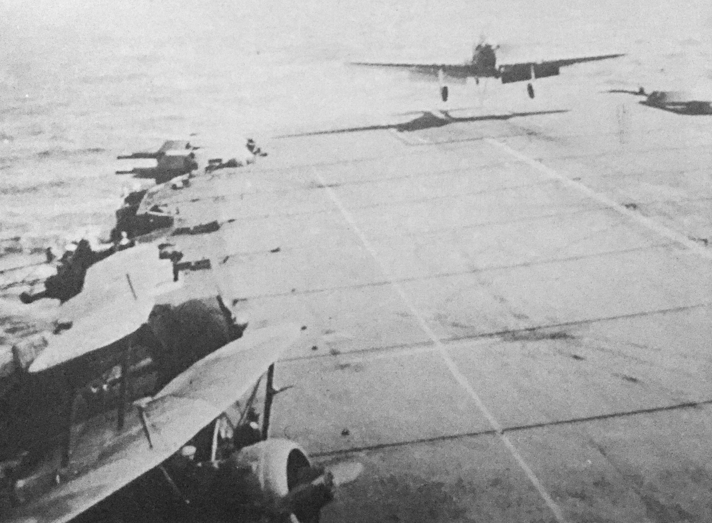 A poor quality but significant photograph as it shows two Sea Gladiators, bottom left, on outriggers while aboard HMS Illustrious during Operation Judgement. A Fulmar is about to touch-down.