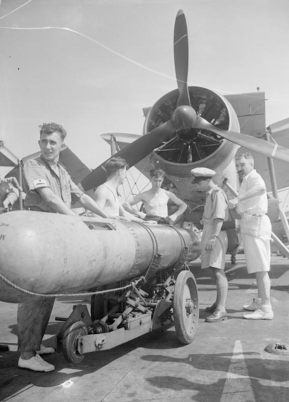 Preparing a Swordfish aboard HMS ILLUSTRIOUS for torpedo dropping exercises.