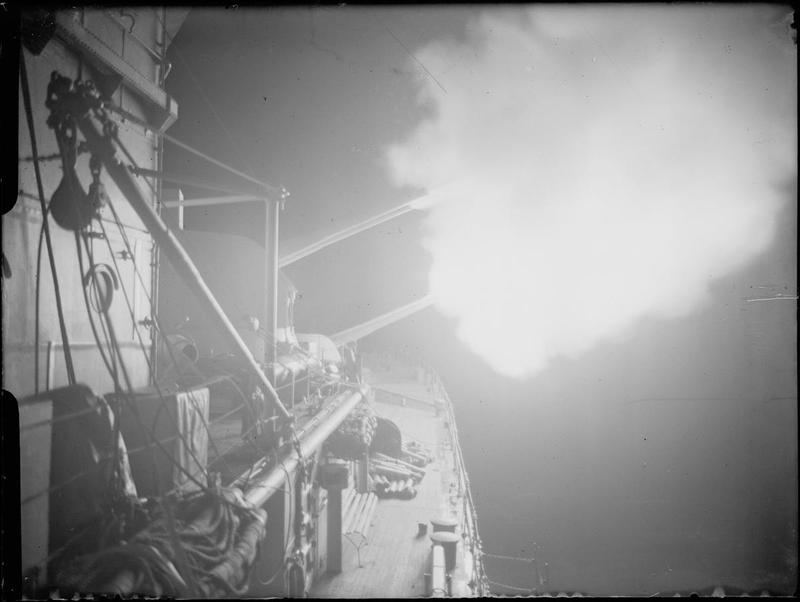 The 6 inch turrets of HMS ORION open fire at night.