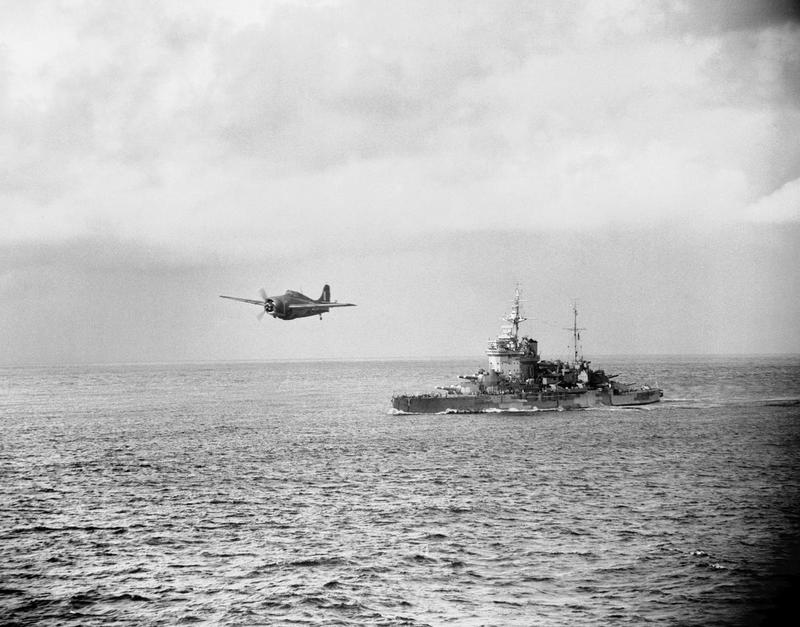 A Grumman Martlet fighter of No 888 Squadron, Fleet Air Arm operating from the aircraft carrier HMS FORMIDABLE, is seen flying over HMS WARSPITE.